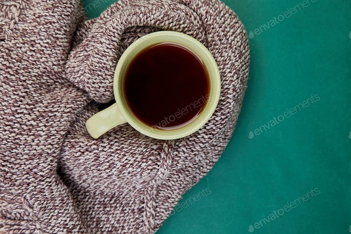 Knitted scarf with warm  cup of tea