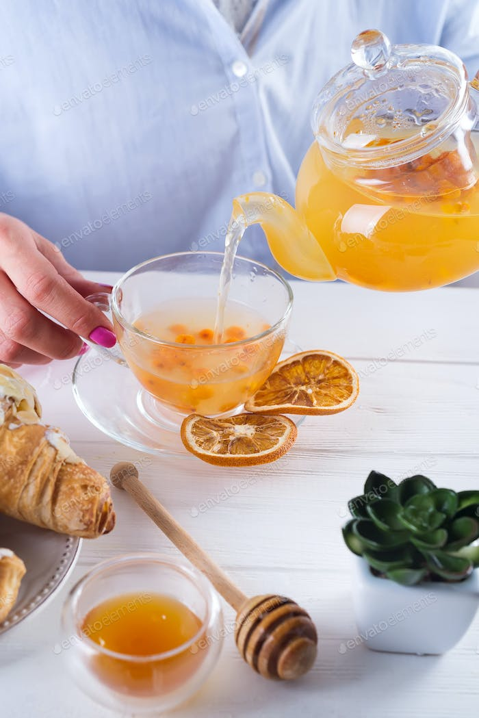 The woman's hands pour sea buckthorn tea on a table with honey and croissants