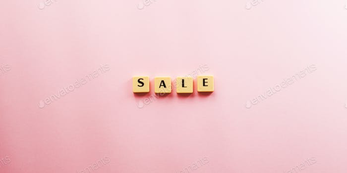 Sale word composed with plastic tiles on pink