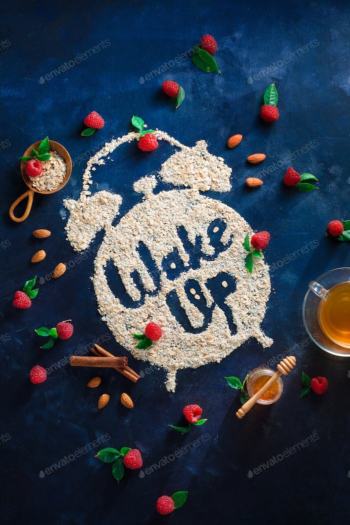 Alarm clock with Wake Up words written with oatmeal, raspberries and cinnamon. Healthy eating