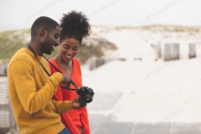 Couple looking at digital camera while leaning against bench on pavement