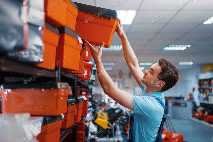 Male employee choosing toolbox in tool store