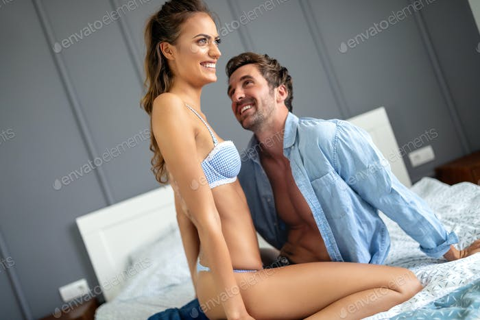 Sensual foreplay by sexy couple in bedroom