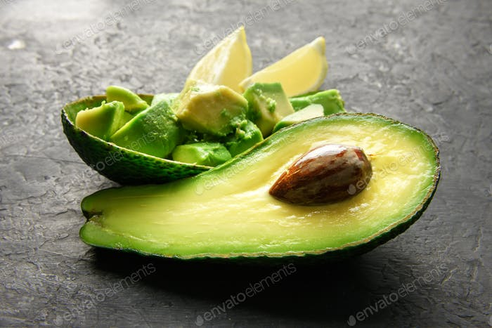 Fresh avocado fruit on a wooden board