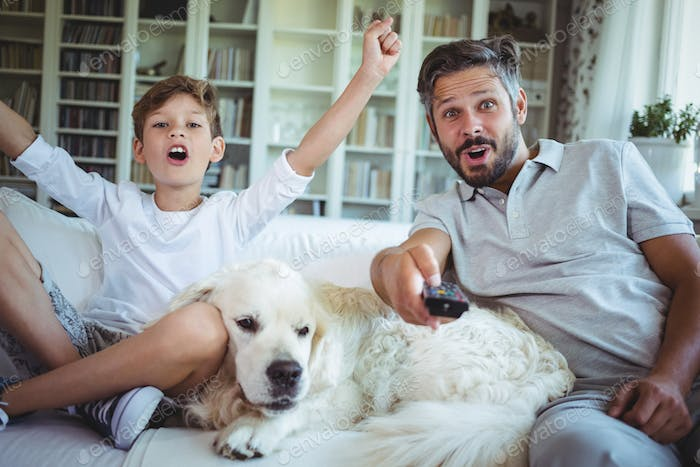 Father and son sitting on sofa with pet dog and watching television