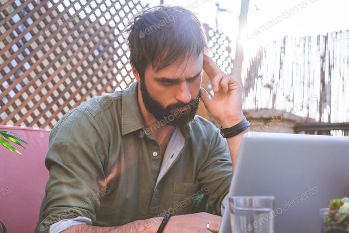 Hipster-Mann arbeitet am Laptop und benutzt Handy, während er auf der Terrasse des Cafés sitzt.