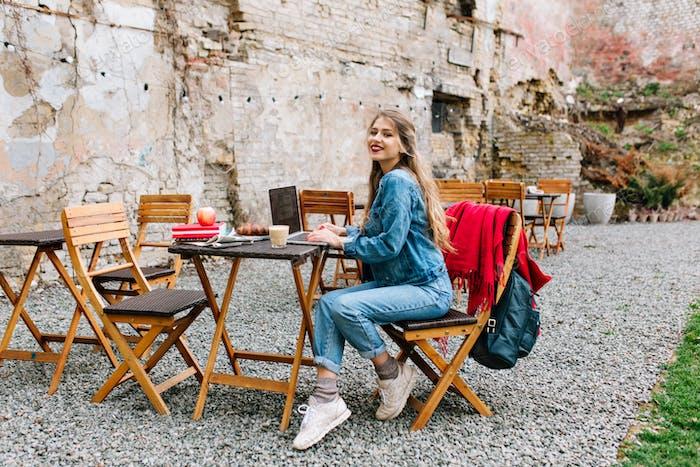 Encantadora rubia freelance mujer usando el ordenador portátil para el trabajo remoto durante el desayuno en el café al aire libre.