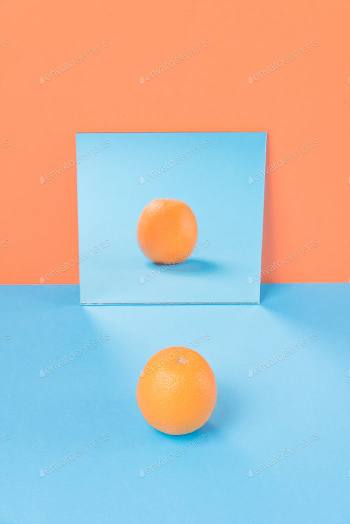 Orange on blue table isolated over orange background