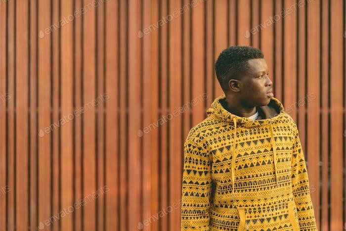 Profilansicht eines jungen schwarzafrikanischen Mannes, der gegen Holztor denkt
