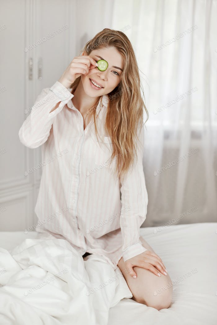 A charming young girl makes a face mask from a cucumber. Skin care. The concept of beauty and health