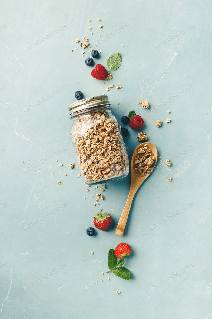 Home granola in a glass jar on blue concrete background
