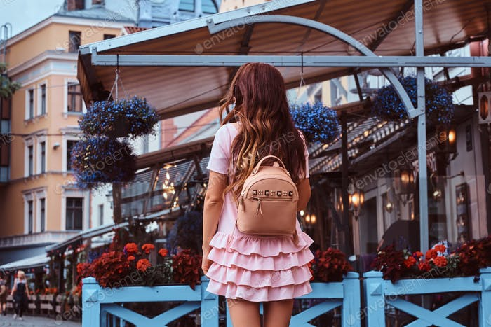 Middle age brunette woman dressed in pink dress posing with rucksack near the terrace cafe.
