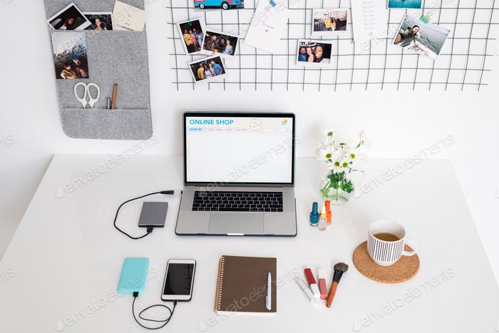 Home page of online shop on display of laptop on designer workplace by wall