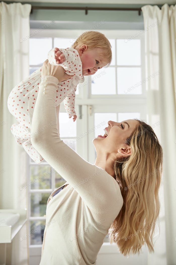 Mother Lifting Baby Daughter In The Air In Nursery