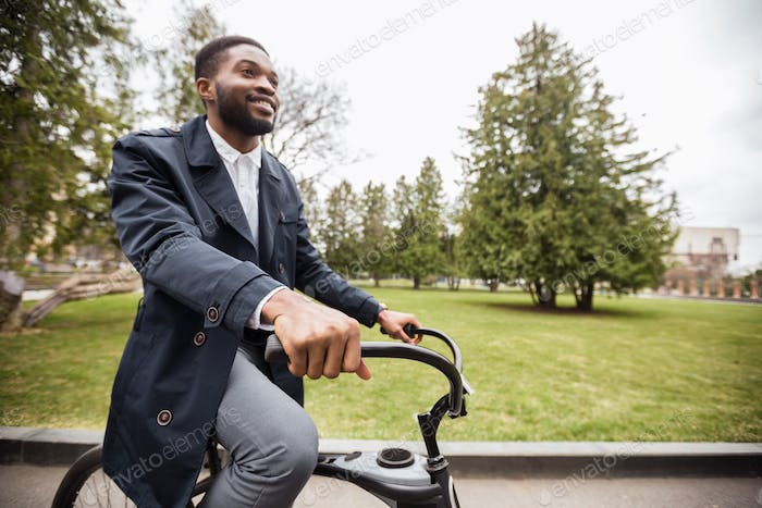 Handsome afro guy riding his bike in park