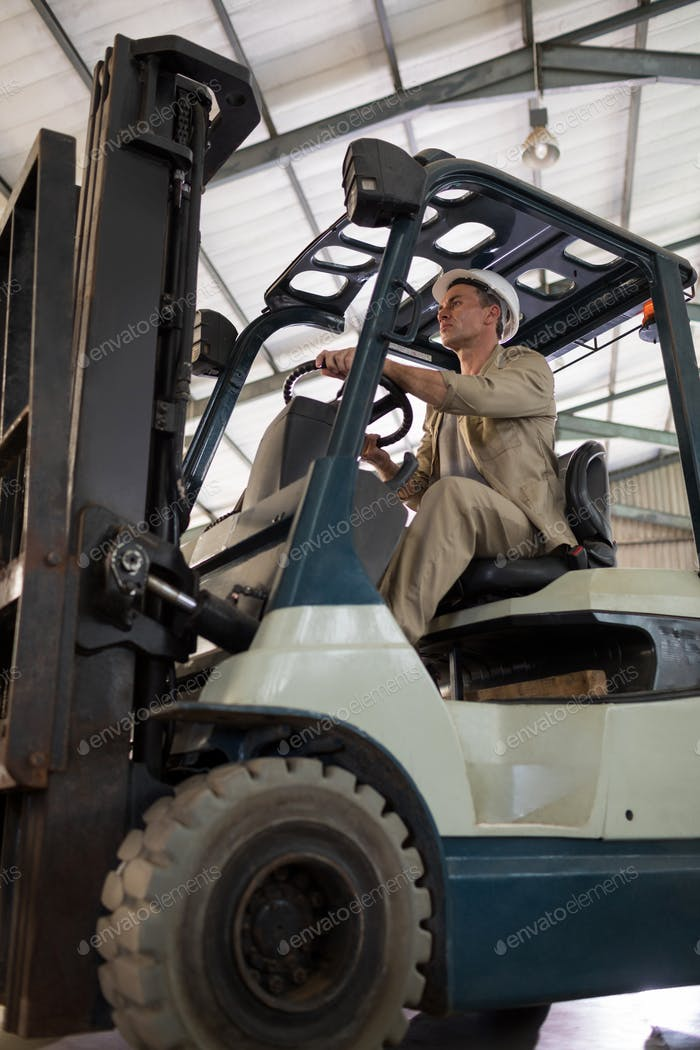 Worker driving forklift