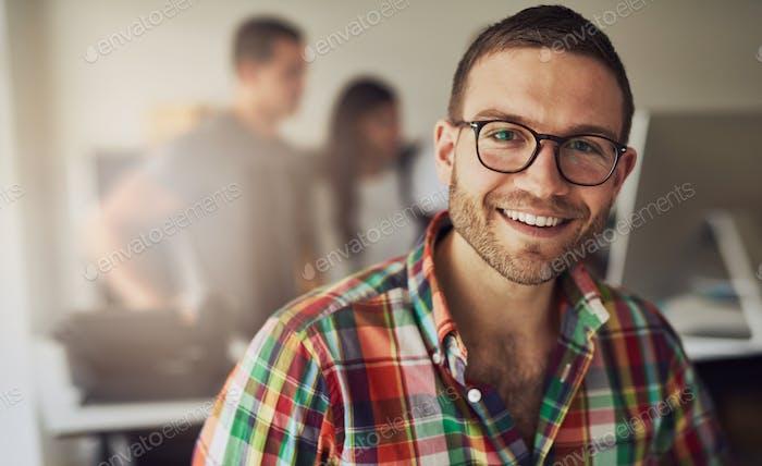Empresario alegre con gafas en la oficina