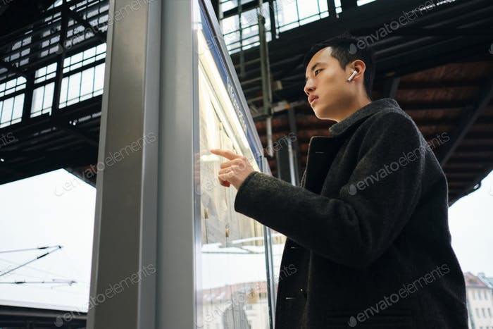 Stylish Asian man in wireless earphones intently watching schedule of public transport at station