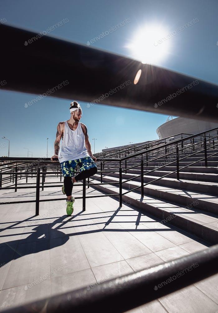 Красивый молодой мускулистый человек в современной спортивной одежде сидит после тренировки на ступеньках рядом с