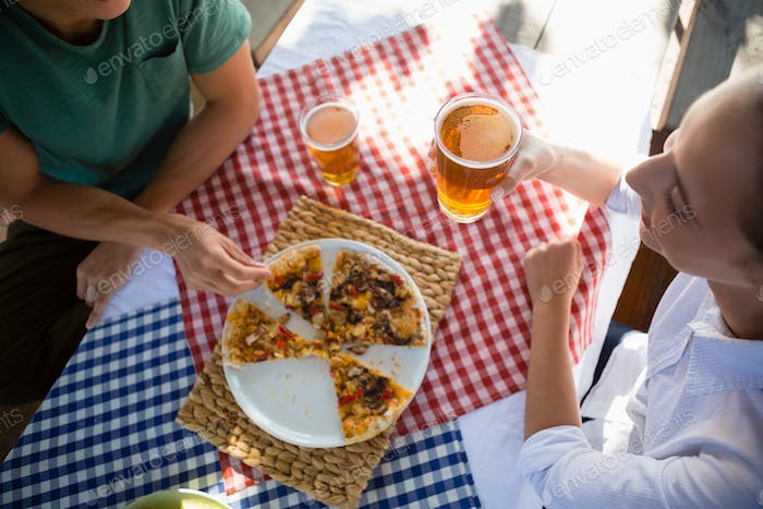 High angle view of friends having pizza and beer