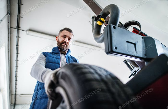 Man mechanic repairing a car in a garage.