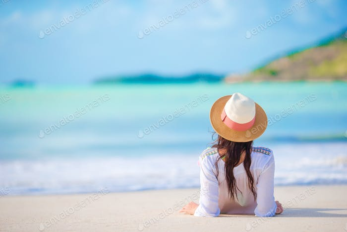 Young woman enjoying the sun sunbathing by perfect turquoise ocean
