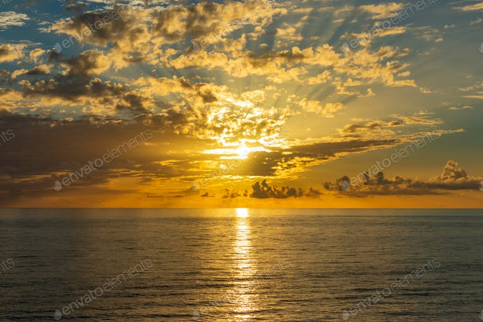 Beautiful sunset over endless sea with reflection in the water