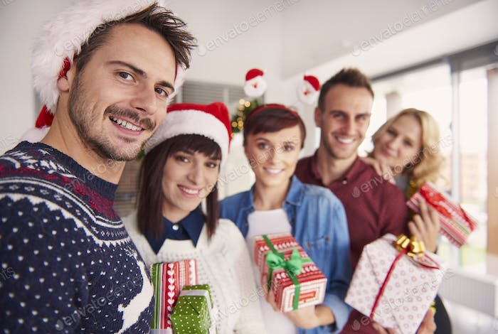 Cheerful young people holding Christmas gifts