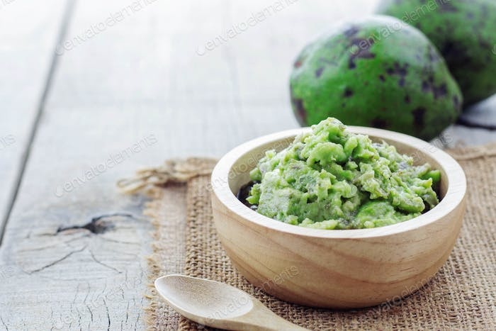 Grated avocado and green on wooden