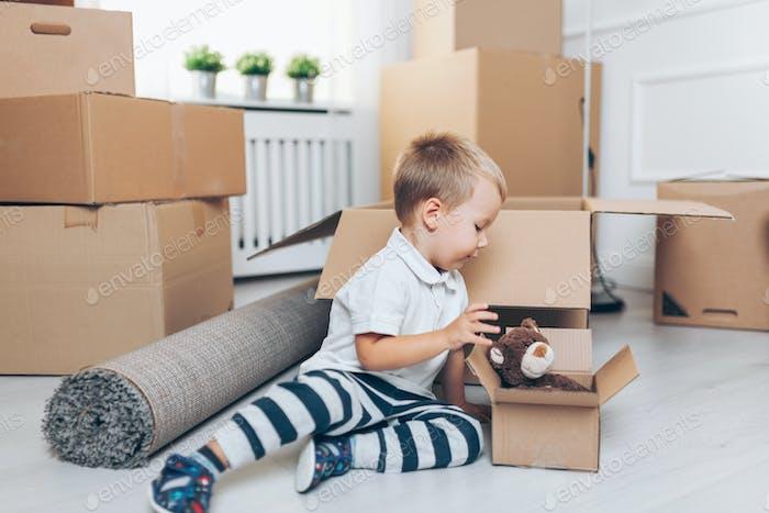 Niedliche Kleinkind hilft Verpackung Boxen