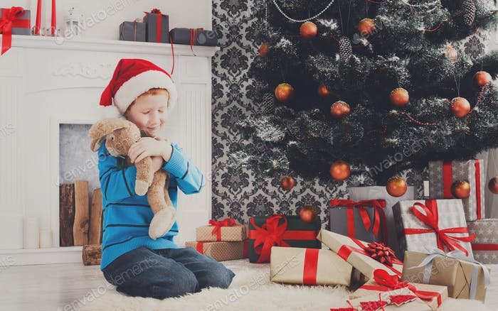 Cute happy boy in santa hat with toy christmas presents