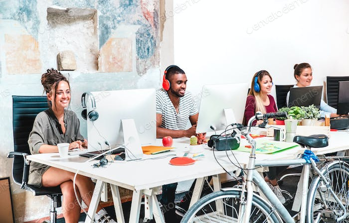 Hipster business people having fun working on computer at coworking space office