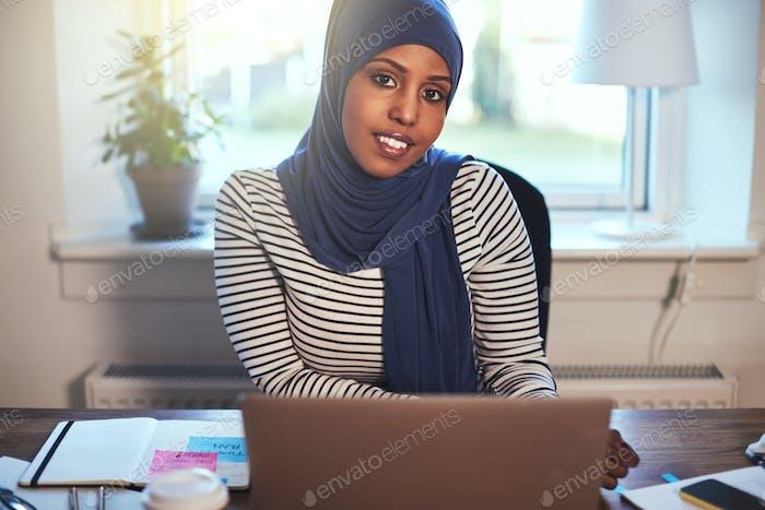 Smiling Arabic female entrepreneur working online in her home office