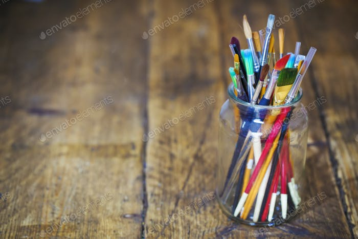 A jar with selection of paintbrushes on a wooden table.