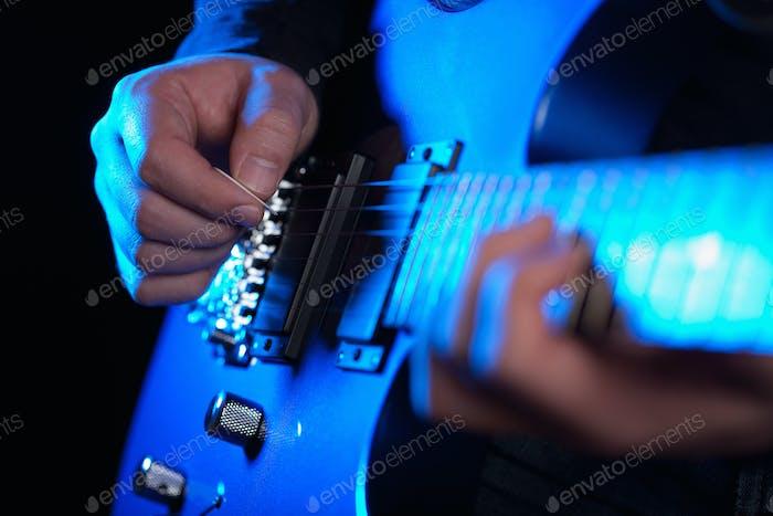musician rock guitarist playing a blue guitar