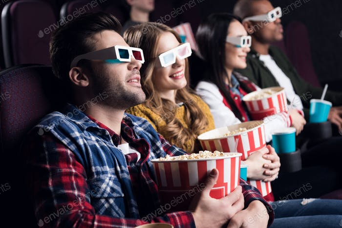 young friends in 3d glasses with popcorn and soda watching movie in cinema