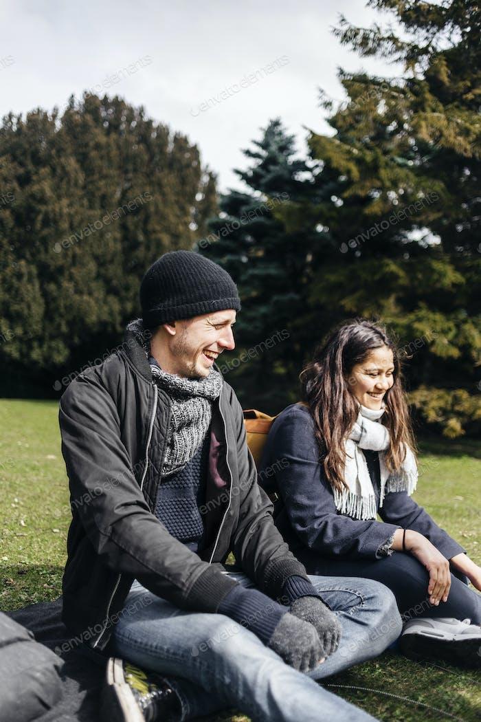 Feliz pareja joven sentado en el parque