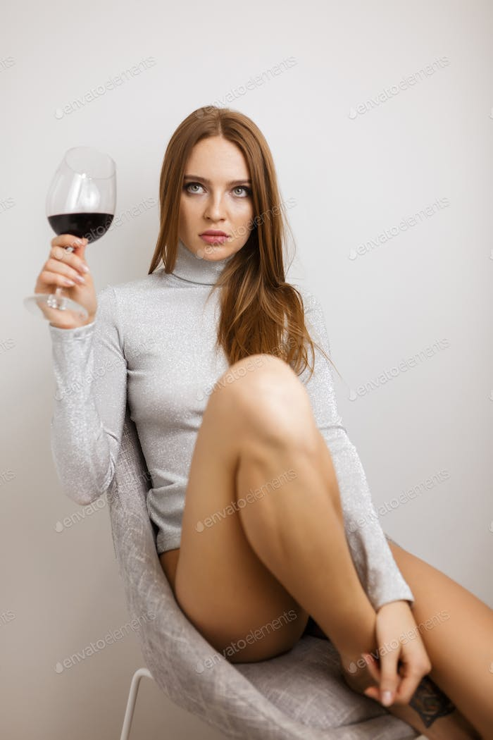 Beautiful lady sitting in chair with glass of red wine in hand thoughtfully looking aside