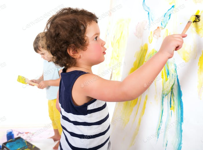 Three children paint with brushes and paints
