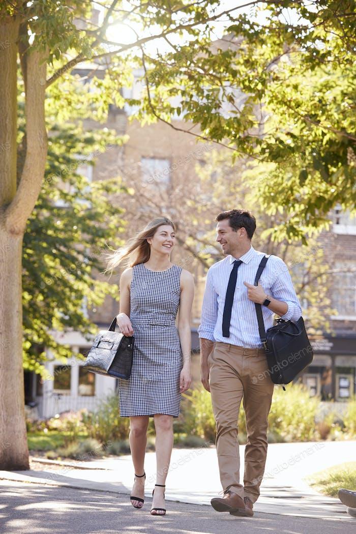 Businessman And Businesswoman Walk to Work Through City Park