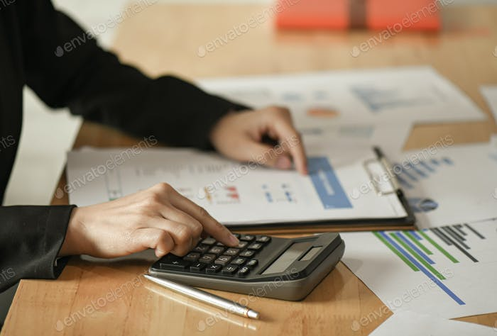 Female businessmen use a calculator , pen to plan a marketing plan to improve the quality.