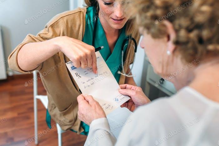 Arzt, der älteren Patienten ein Rezept gibt
