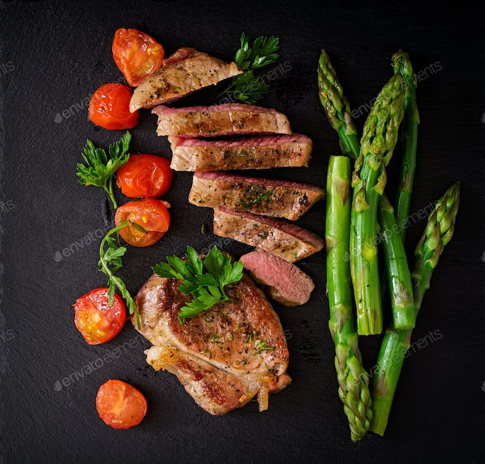 Juicy steak medium rare beef with spices and  tomatoes, asparagu