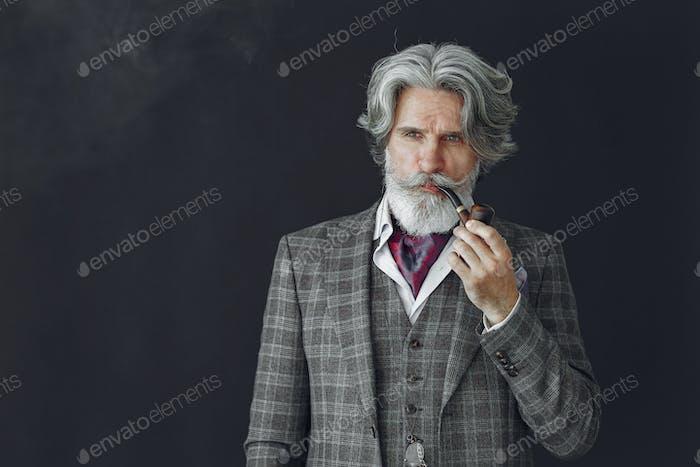 Eleganter Seniorenmann mit einer Pfeife