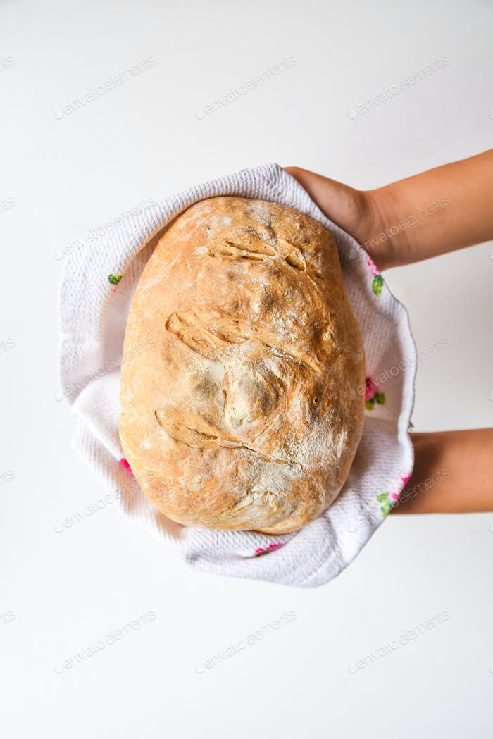 Woman's hands holding freshly homemade baked bread, top view