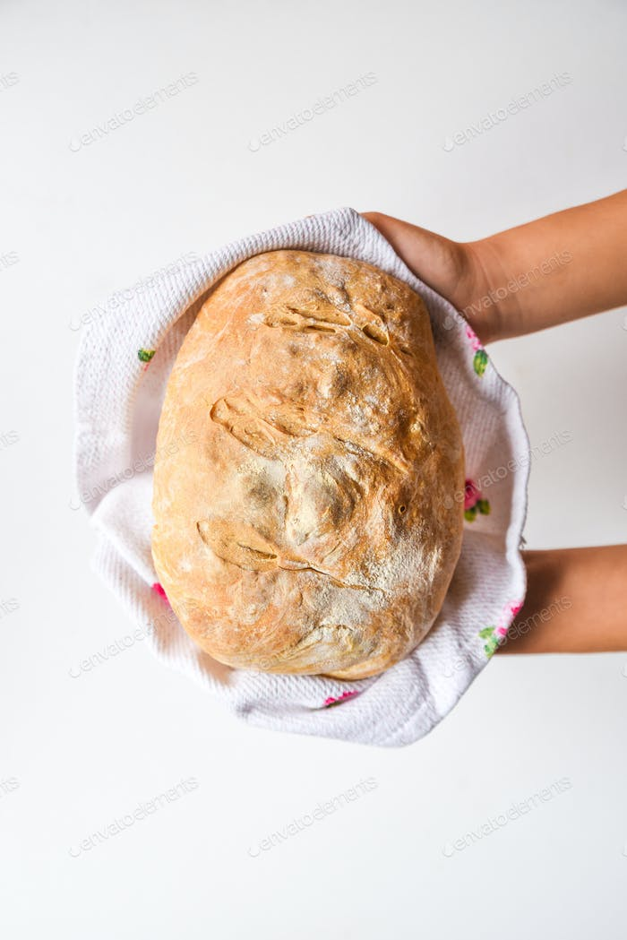 Frauenhände mit frisch hausgemachtem gebackenem Brot, Draufsicht
