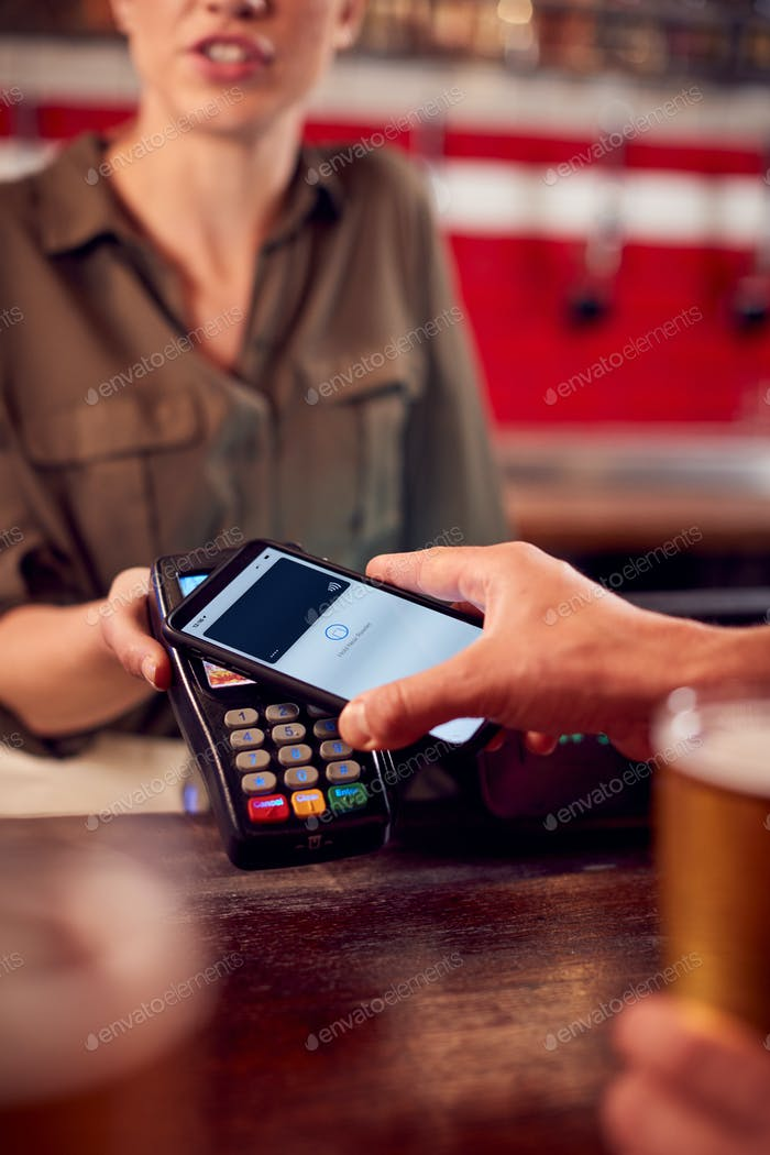 Close Up Of Man Paying For Drinks At Bar Using Contactless App On Mobile Phone