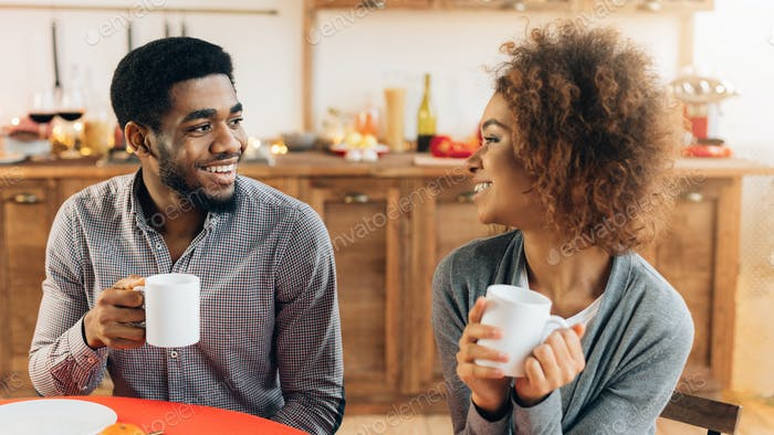 Couple enjoying cup of coffee together in kitchen