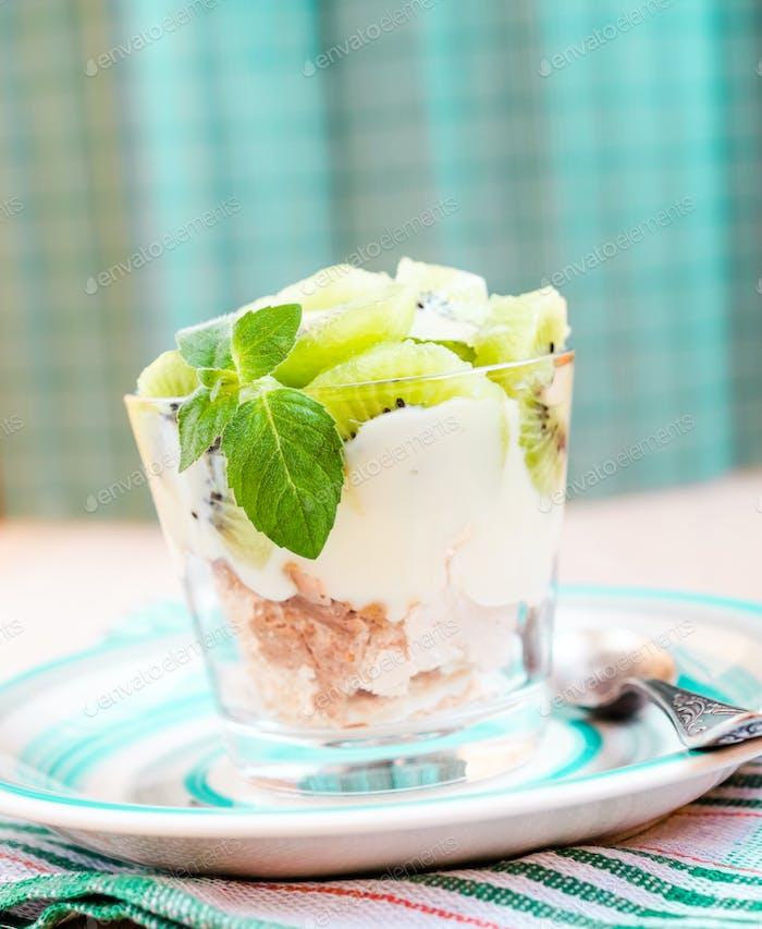 Kiwi Eton mess - dessert with meringue, whipped cream and fruits