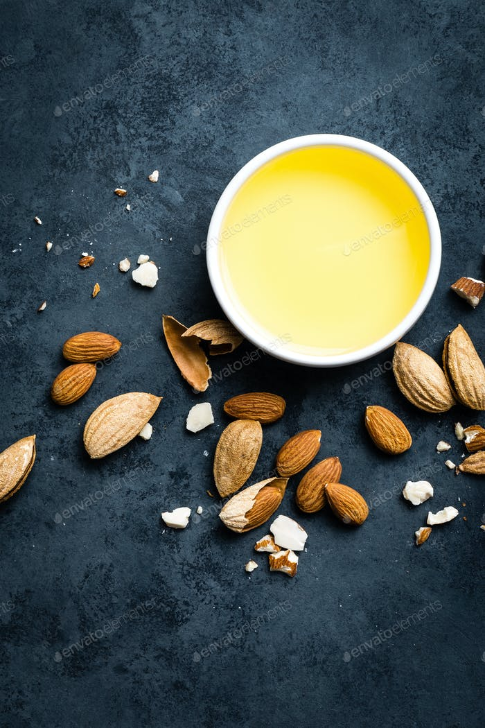 Almond oil in bowl and almond nuts. Almonds